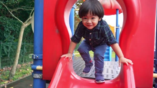 asian boy (2-3 years) having fun sliding - 2 3 years stock videos & royalty-free footage