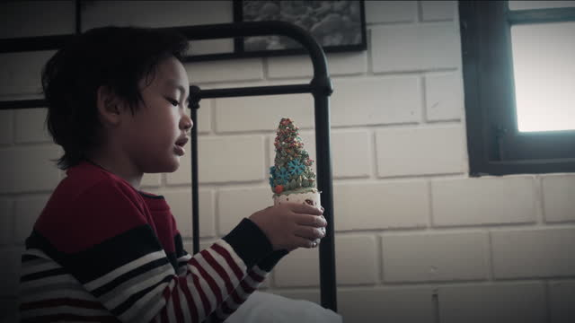 vídeos de stock, filmes e b-roll de garoto asiático segura cupcake de natal no quarto. - só um bebê menino