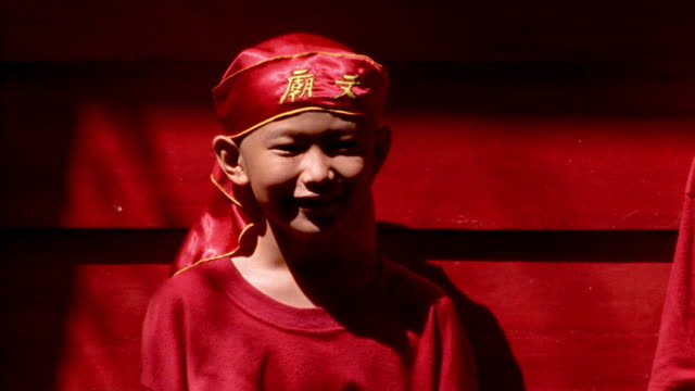 MS PORTRAIT Asian boy in red costume + hat (dragon dancer) laughing / red background / Java, Indonesia