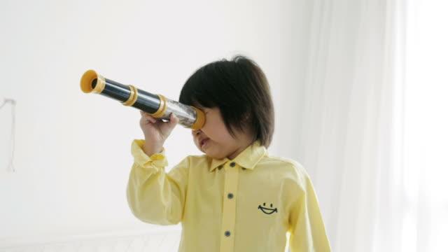 asian boy is looking through the binoculars - stock video - binoculars stock videos & royalty-free footage