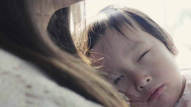 Asiatische junge ist schläfrig und so tun, als mit ihrer Mutter im Auto schlafen, während sie auf Reisen gehen