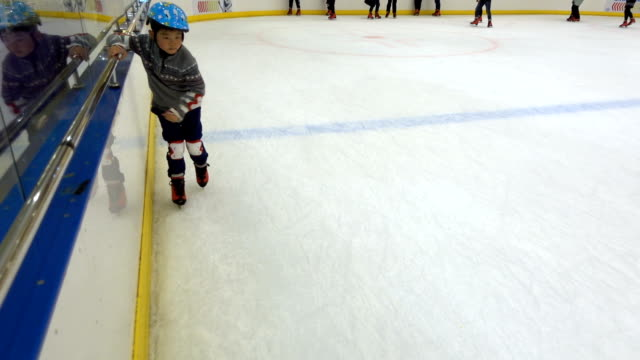 asian boy learning to skate indoors - winter sport stock videos & royalty-free footage