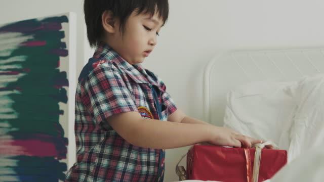 クリスマス プレゼントのアジアの少年のオープン ギフト ボックス - 小荷物点の映像素材/bロール