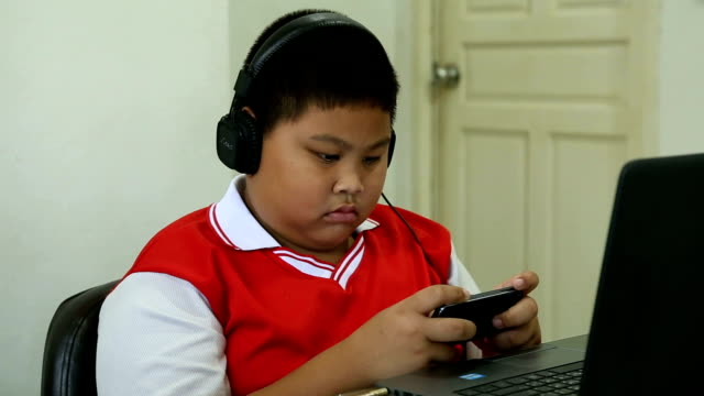 Asian boy playing game on mobile phone format VDO HD.