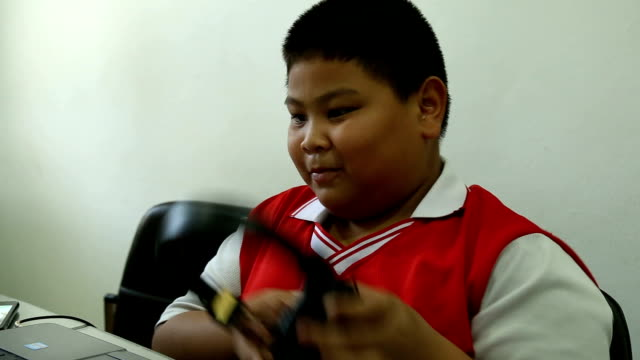 Asian boy playing laptop and put in headphone format VDO HD.