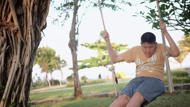 asian boy playing on a swing and having fun in park , slow motion. - swinging stock videos & royalty-free footage