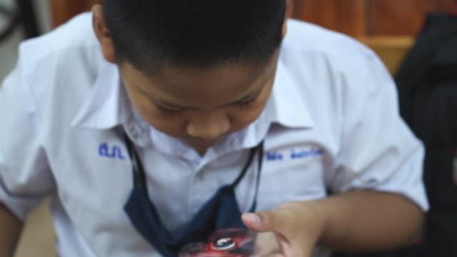 アジアの少年は、娯楽と楽しみのためにスピナーを果たしています。 - 注意欠陥過活動性障害点の映像素材/bロール