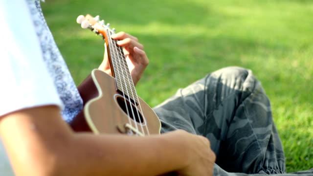 stockvideo's en b-roll-footage met aziatische jongen speelt ukulele in het park - alleen jongens