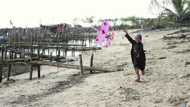 asian boy playing with his traditional kite.he running on the beach. - baby boys stock videos and b-roll footage