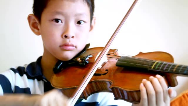 vídeos de stock, filmes e b-roll de rapaz asiático toca violino em casa - extremo oriente