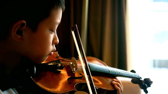 asiatiska boy spelar fiol hemma