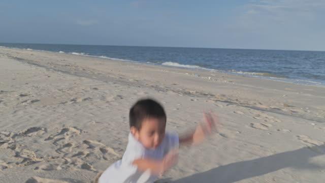 vídeos de stock, filmes e b-roll de passeio praticando do menino asiático em uma praia arenosa com luz do sol morna. - moving down