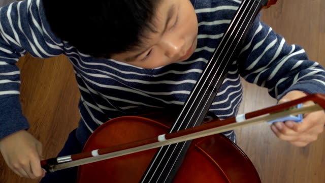 asian boy putting rosin on cello bow - tied bow stock videos & royalty-free footage