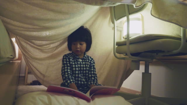 asian boy reading a fairy tale with flashlight under a blanket fort - fortress stock videos & royalty-free footage