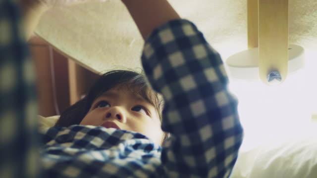 vídeos y material grabado en eventos de stock de chico asiático leyendo un cuento de hadas con linterna bajo un fuerte manta - almohada