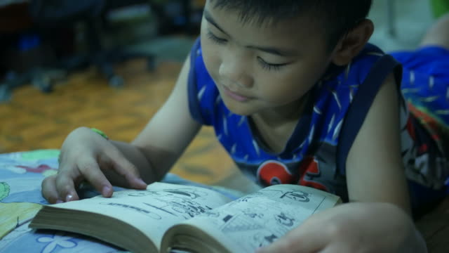 asian boy reading book in bedroom - saggezza video stock e b–roll