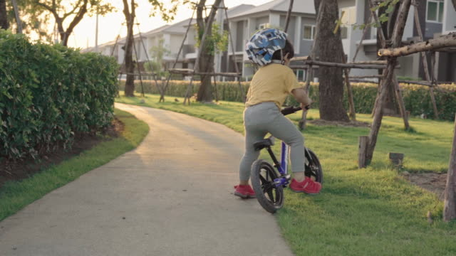 asian boy riding a bicycle at garden - baby boys stock videos & royalty-free footage