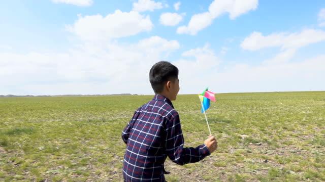 asian boy running with windmill in grassland - girandola video stock e b–roll