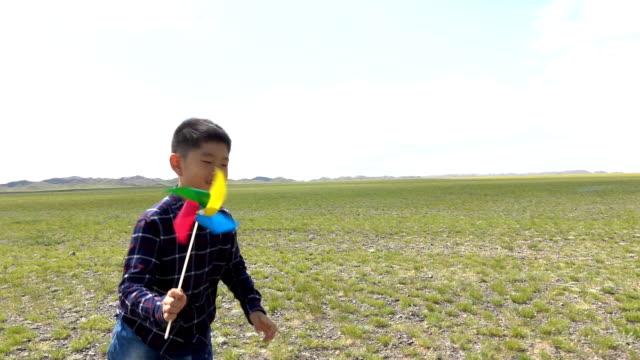 stockvideo's en b-roll-footage met aziatische jongen rennen met windmolen in grasland - alleen jongens