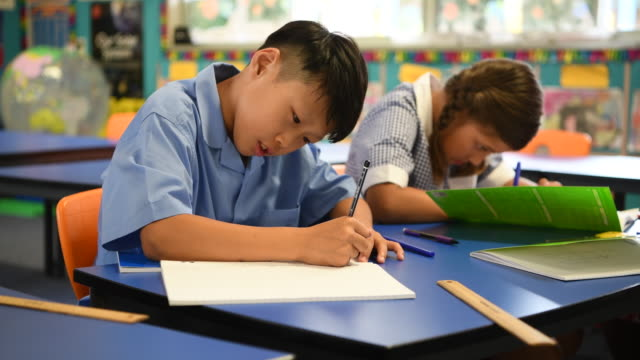 asian boy sitting at desk and writing in his school book - primary school child stock videos & royalty-free footage