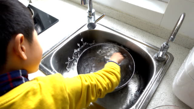 Asian boy stirring water at home