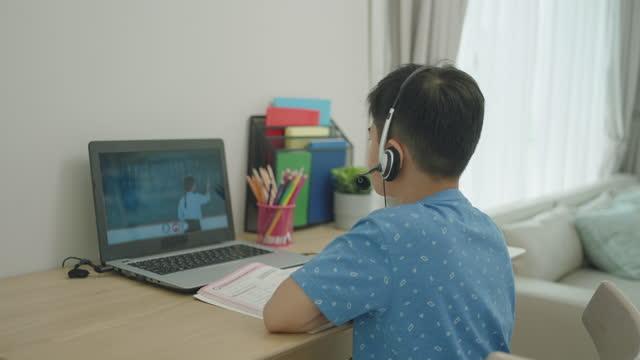 vídeos de stock, filmes e b-roll de o menino asiático estudou matemática com professor online via laptop e olhando para camare na sala de estar da casa durante a escola em casa enquanto a escola estava fechada devido ao surto de covid-19. - criança de escola fundamental