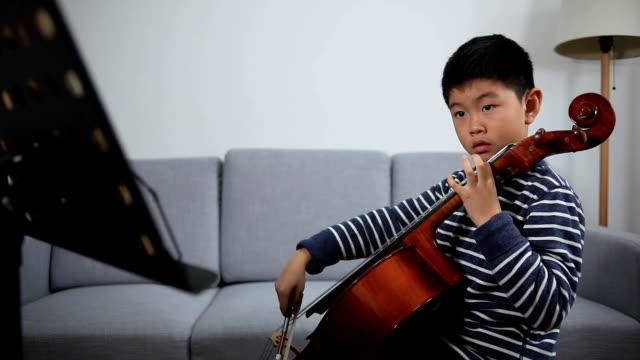 asiatischer junge studiert cello im haus - schnur stock-videos und b-roll-filmmaterial