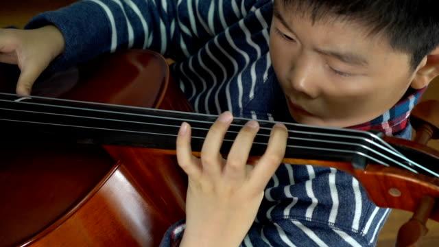 vidéos et rushes de garçon asiatique étudiant le violoncelle à l'intérieur - violoncelle