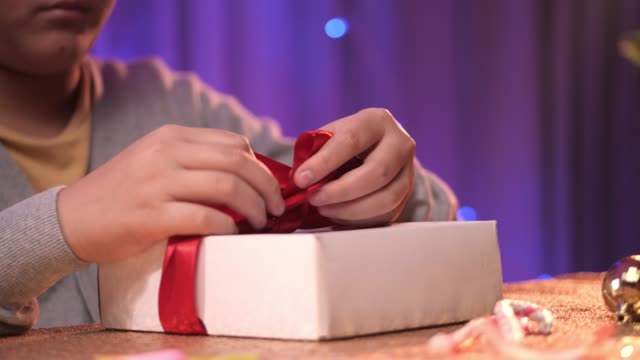 asian boy tied red bow on gift box for preparing christmas party. - tied bow stock videos & royalty-free footage