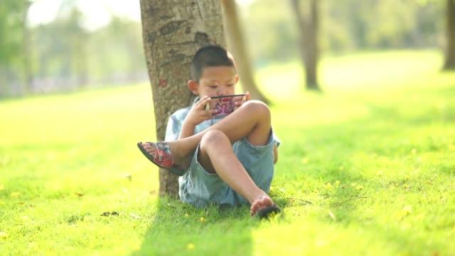 vídeos de stock, filmes e b-roll de menino asiático que usa o jogo digital com o telefone esperto no jardim - pré adolescente