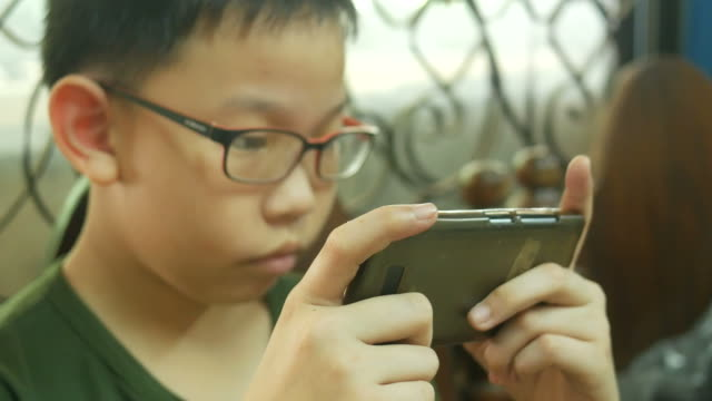 asian boy using digital game with smart phone - candid stock videos & royalty-free footage