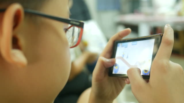 asian boy using digital game with smart phone - contestant stock videos and b-roll footage