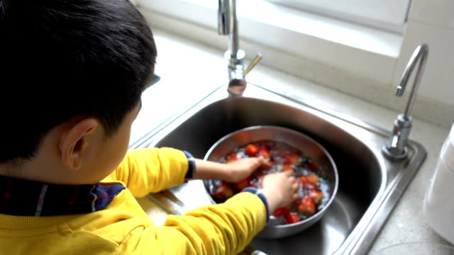asian boy washing strawberry at home - utensil stock videos & royalty-free footage
