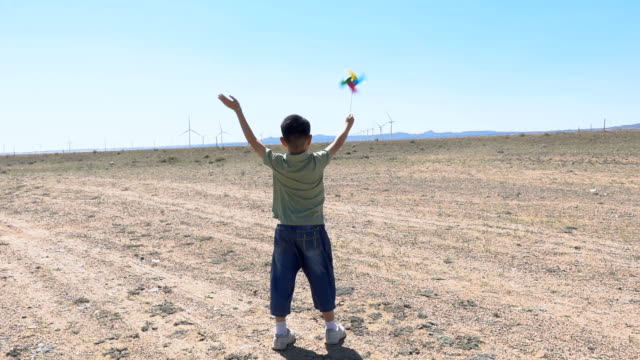 asian boy waving hand with windmill towards wind farm - waving gesture stock videos & royalty-free footage