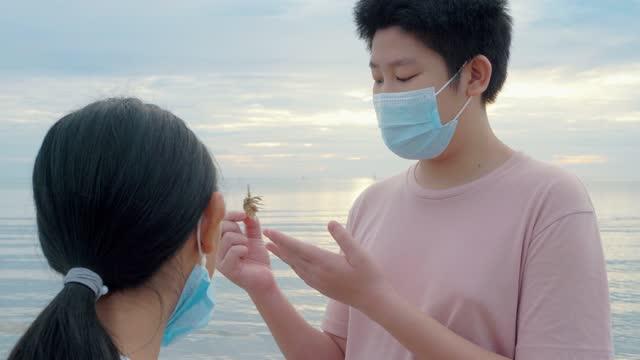 フェイスマスクを着用したアジアの少年は、日の出とビーチでヤドカリの手をキャッチ。男の子は、ヤカリ、ライフスタイルの概念について彼の妹に話します。 - カニ捕り点の映像素材/bロール