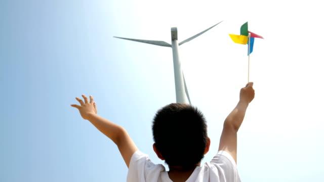 asian boy with pinwheel toy facing windmill - girandola video stock e b–roll