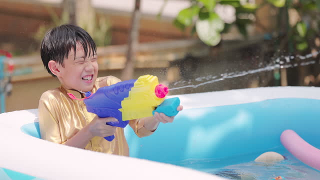 asian boy with traditional thai dress playing water gun in the water pool at summer time - water fight stock videos & royalty-free footage