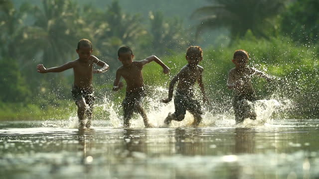 asian boys having fun playing in the river with splashing water together.(slow motion) - povertà video stock e b–roll