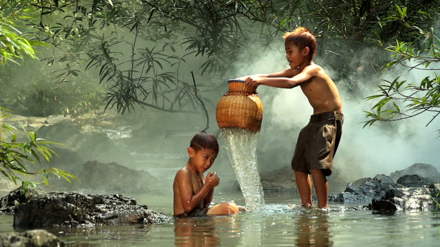 vídeos de stock e filmes b-roll de hd: asian boys having fun playing in the waterfall. - poverty