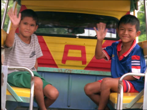 portrait 2 asian boys smiling + waving to camera from backseat of truck / thailand - thai ethnicity stock videos & royalty-free footage