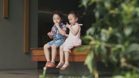 asian brother and sister are eating snack at the corridor - sharing stock videos & royalty-free footage