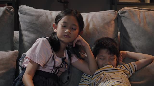 asiatischer bruder und schwester fernsehen zu hause in der nacht - fade in video transition stock-videos und b-roll-filmmaterial