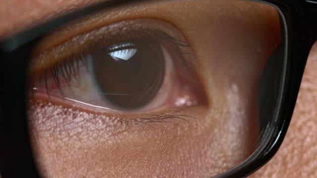 ecu asian brown eye looking through glasses - eyewear stock videos & royalty-free footage