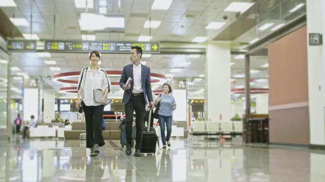 空港でアジアのビジネス同僚とシニアカップル - passenger点の映像素材/bロール