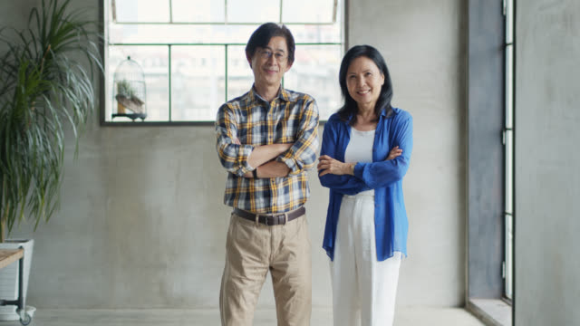 Asian Business Couple Smiling and Folding Arms
