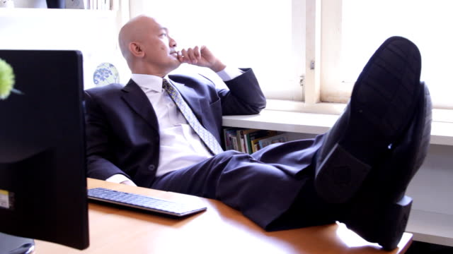 Asian business executive thinking at desk