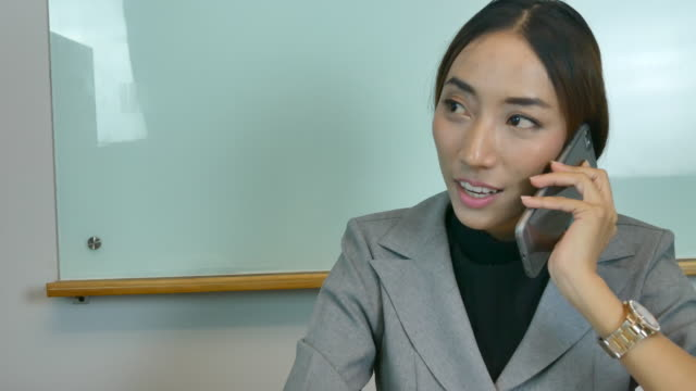 asian business girl in suit talking on mobile phone in office