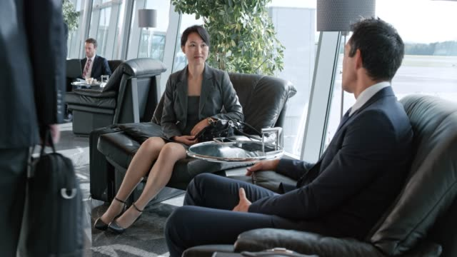 ds asian business man and woman  sitting in the business lounge at the airport and talking - armchair stock videos & royalty-free footage