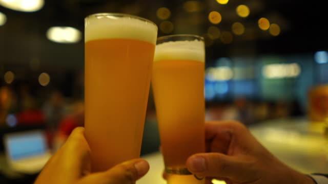 ナイトクラブでビールを飲むアジアのビジネスマン、一緒に歓声 - ガラス点の映像素材/bロール