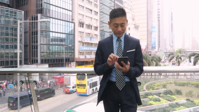 asian business man using a mobile phone - chinese ethnicity stock videos & royalty-free footage